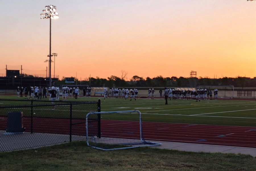 Running to the center of the field, varsity, junior varsity and freshman football players prepare for their next drill. The teams participate in their