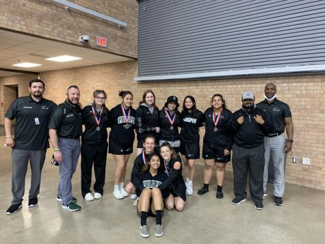 The varsity girls wrestling team gathers following their district-meet wins. The girls team had six girls place in the top three of their brackets. They will continue to the regional competition. Two girls hold the alternate spots for regionals. Allen High School hosted the district tournament  April 9-10. Pictured is Coach Frescas, Coach Cooper, Ashley Vogelpohl, Delia Luna, Meghan Flaherty, Katherine Hall-Smith, Andrea Garcia, Lauren Garst, Taylor Martinez, Ciera Stuver, Alyssa Galiendo, Coach Cabet, and Head Coach King.