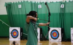Drawing his bow, senior Ethan Doucet shoots from the 15 meter line. Doucet has played with Prosper High School archery since his freshman year. To honor the seniors during this tournament, they wore green senior shirts instead of the gray team ones.