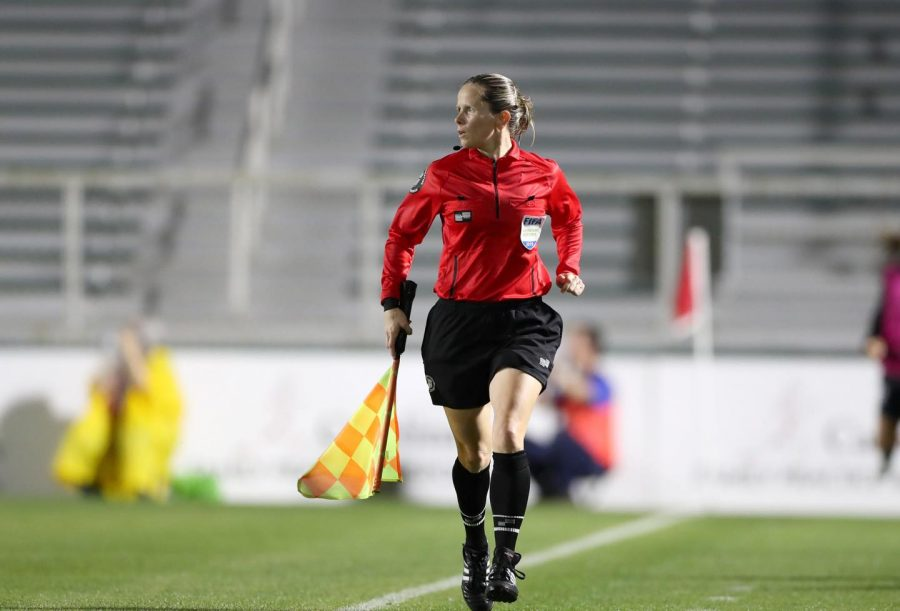 Running along the sideline, teacher and coach Jennifer Garner watches the match. Garner has been a professional referee since 2013 and received her FIFA badge in 2018.