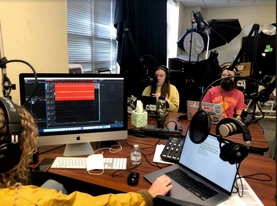 In an image taken by journalism advisor, Lisa Roskens, seniors Caroline Wilburn, Emma Hutchinson, and junior Christi Norris record the latest episode of History