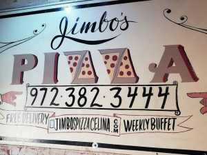 The Jimbo's Pizza sign hangs on the wall on the stage. One of the owner, Dago Rodriguez's, close friends made this sign for him.
