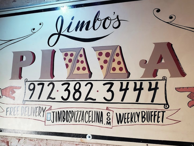 The+Jimbo%27s+Pizza+sign+hangs+on+the+wall+on+the+stage.+One+of+the+owner%2C+Dago+Rodriguez%27s%2C+close+friends+made+this+sign+for+him.+%22I+came+to+Jimbo%27s+for+pizza+and+left+with+a+life+long+friend%2C%22+customer+Ben+Jones+said.+%0A%22Something+I+learned+later+was+his+pizza+was+how+he+gets+everyone+to+do+what+he+wants.+So+I+decided+to+%27hang%27+around%2C+hoping+to+find+out+his+secret+for+making+pizza.%22