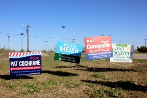 Waving in the wind, four school board election campaign signs stand on one side of Prosper High School. This year, there are five candidates running for Place 4, and two candidates running for Place 7. Early voting is held April 19-27, and is followed by election day May 1.