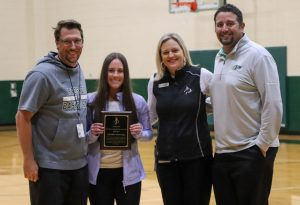 Standing with girl's basketball coach Trey Rachal, Director of Athletics Valerie Little and girl's golf coach Ryan Salinas, senior Chandler Browning accepts her