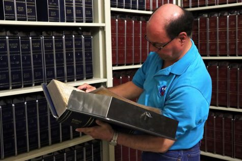 """Paul """"Tinker"""" Rosales reads a marriage record contained in a disaster-safe binder, stored in the shelves beneath the Collin County Courthouse. Rosales, part of a team of county employees led by county clerk Stacey Kemp, works with the office team to preserve records from 1800 to the present day. Collin County"""