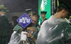 Wearing a poncho to stay dry from the rain, senior Sophia Ross, who plans to attend Brigham Young University in the fall, hugs a teacher.  Junior Ailee McFarland started a small business making graduation caps for seniors.