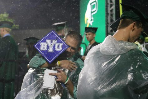 """Wearing a poncho to stay dry from the rain, senior Sophia Ross, who plans to attend Brigham Young University in the fall, hugs a teacher.  Junior Ailee McFarland started a small business making graduation caps for seniors. """"Basically, I helped my best friend make her older sister"""