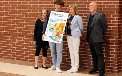 To celebrate a publication accomplishment, adviser Lisa Roskens, senior Mark Chrissan, superintendent Holly Ferguson and senior designer Gary Garrett, take a minute to let Chrissan show his designs, which recently won an award.  Chrissan holds a poster of his design that represents the cover of Medical City Children's Hospital's