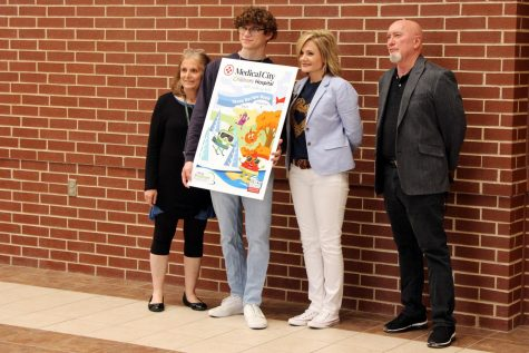 To celebrate a publication accomplishment, adviser Lisa Roskens, senior Mark Chrissan, superintendent Holly Ferguson and senior designer Gary Garrett, take a minute to let Chrissan show his designs, which recently won an award.  Chrissan holds a poster of his design that represents the cover of Medical City Children