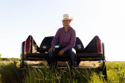 Sitting in the bed of his truck for his senior pictures, senior Joshua Walker smiles. Walker plans to follow in his cousin