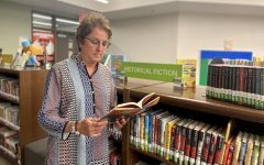 """Standing in front of her favorite spot, librarian Terri Harkey reads a book from the historical fiction section titled, A Long Walk To Water by Linda Sue Park. After being a band director and musician, Harkey found another career shes passionate about, and has now been a librarian for 14 years. A Long Walk to Water is one of my favorites,"""" Harkey said. I love the story it tells."""