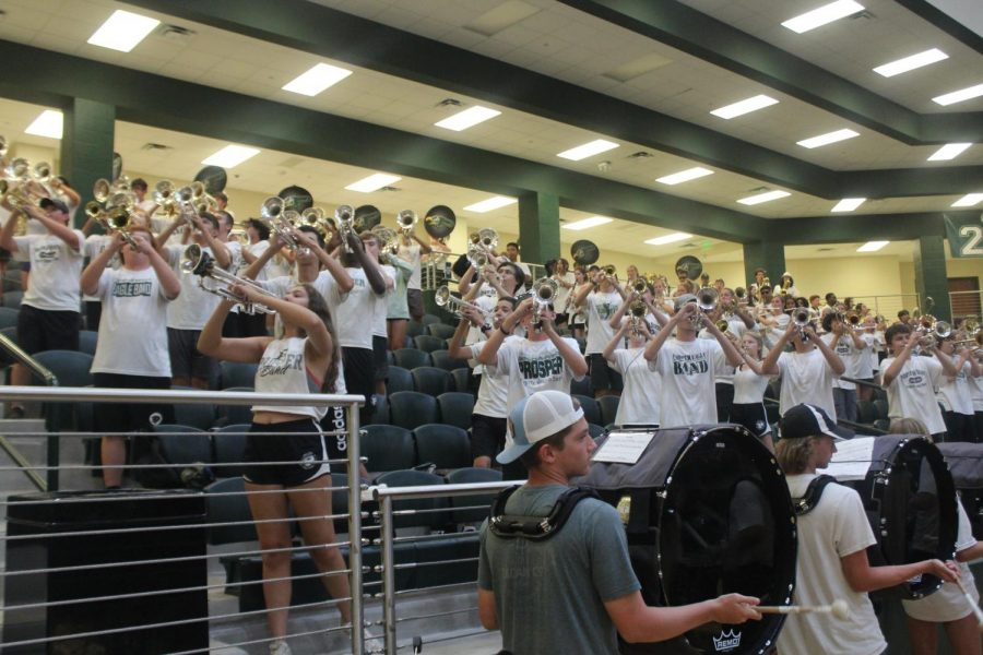 Instruments in the air, the Prosper Mighty Eagle Band performs during the new student pep rally Thursday, Aug. 5. This gathering marked one of the many programs created this year to welcome students to the school. I was really excited about the freshman/new student pep rally because it presented a great opportunity to help students feel welcome and be immersed into the Eagle Nation environment, spirit leader organizer Natalie Merrill said. We want to continue to foster an engaging sense of school spirit, and pep rallies are a perfect way to do so.