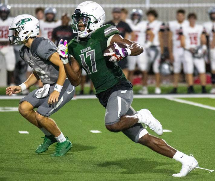 During the Aug. 23 scrimmage against Flower Mound Marcus, senior Tyler Bailey looks to avoid Marcus defensive players as he runs toward the end zone. Bailey, one of this years team captains, serves with other captains and seniors Nash Gagliano, Kaleb Miles and Aeden Combest.