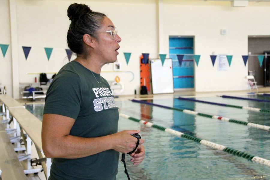 """Timer in hand, head swim coach Lena Harrington gives directions to swimmers in the pool before their timed practice. This is Harringtons first year at Prosper leaving Plano ISD after nine years. """"I sat and got to speak with Coach Little, Coach Schmidt and Coach Sacco, all the coaches,"""" Harrington said. """"It just felt like home."""