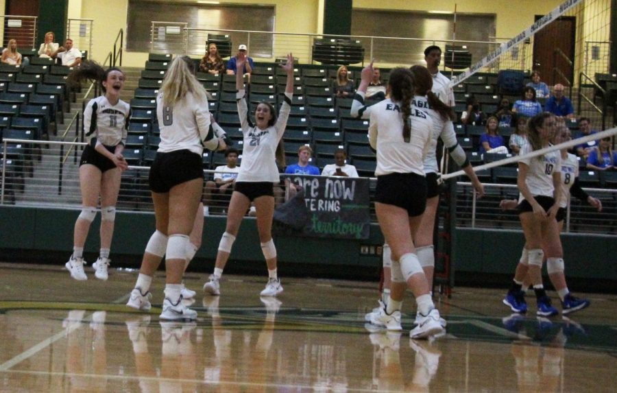 Celebrating a win, the varsity volleyball team throws their hands up. Students who came and filled up the stands got free pizza. We really took control of that first set. By extending the lead the first half of the set. Then we can relax a bit in the second half. If we make a few errors thats okay. We still have a healthy lead, head coach Erin Kauffman. Were playing really well right now. Were playing hard. Our defense is better than its been in a while. Our passing looks good, and overall Im really happy with what were doing.