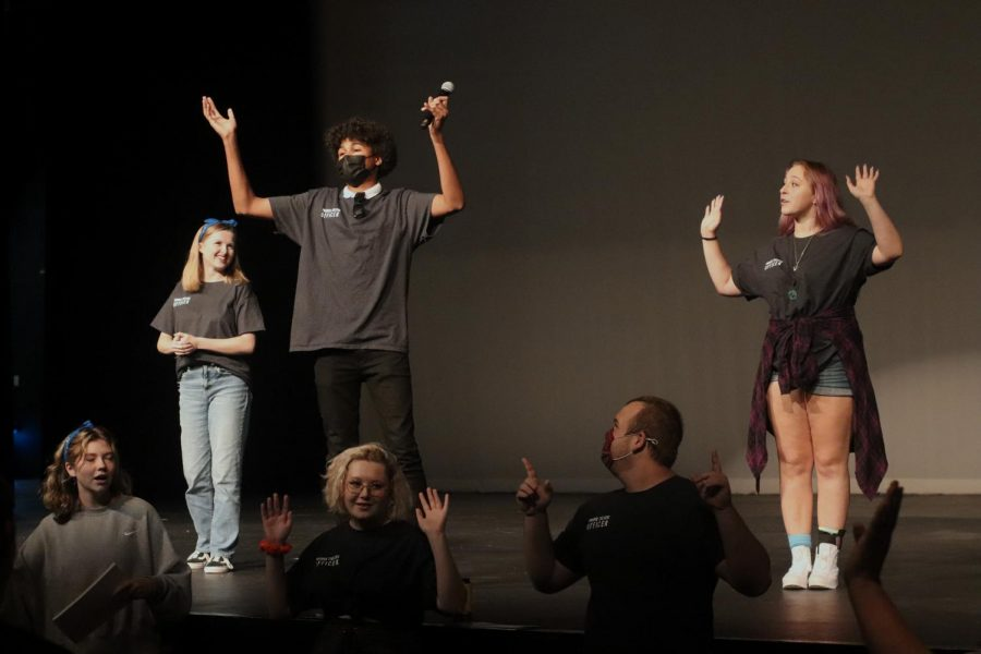 Arms raised in the air, senior Alex Oshunkentan leads everyone in a group warm up prior to the social starting. This is Oshunkentans second year in the department, snf he is the leader of the Procyon house. The social was held  Aug. 26 in the auditorium.