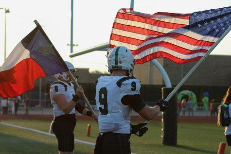 Waving a U.S. flag, senior Aeden Combest stands beside junior Dylan Hinshaw during the National Anthem. The varsity football team played Friday, Sept. 17 against Arlington Lamar.