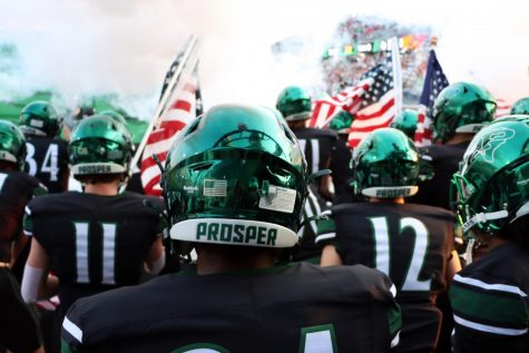 Smoke billowing above them, juniors Carson McClendon and Caden Pevehouse stand with their team waiting to run onto the field. At Fridays game, Prosper players carried 15 American flags onto the field. Two of these flags represented the world trade centers lost on September 11, 2001, and 13 represented the 13 U.S. servicemen recently killed in Afghanistan.
