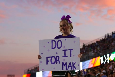 Performing a stunt, junior Kendall Smith holds a sign in honor of fellow cheerleader Makayla Noble. Noble recently injured her spinal cord in a tumbling accident and is currently hospitalized. Community members, staff and students wore purple to the game Sept. 24 in her honor.