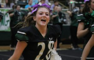 Getting the crowd excited, junior and varsity cheerleader Ava Haworth completes a cheer. All the cheerleaders wore purple bows saying Be Noble to honor their teammate, senior Makayla Noble. They also held up signs that said Do It for Mak.