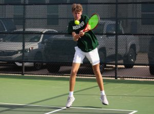 Jumping to hit the ball, senior Drew John returns it back over the net. This year marks Johns third season playing for the varsity team. John covered the back end of the court on this doubles match alongside Elijah Steur during the home matchup against McKinney High.