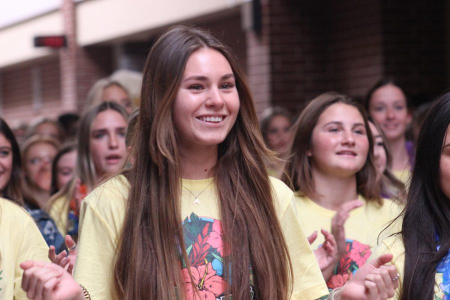 Walking down the hall, senior varsity cheerleader Kallie Knight cheers in the send-off. The send-off occured in place of the Hawaiian pep rally Thursday, Aug. 2. The cheerleaders wore yellow shirts and leis for the spirit day.