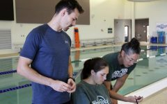 Helping his athletes log their lap time, assistant swim and dive coach Keenan Fogelberg gives advice. This is Fogelbergs first year coaching at Prosper. Before this I was in Dallas and before that I was in Orem, Utah, Fogelberg said. Yes I have coached football before officially and I unofficially helped out freshman soccer as well.