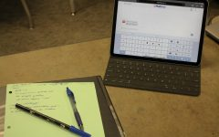 Laying on a desk sits pens, paper and a device using the Mathway app. The set-up illustrates many students point of view every day. Mathway acts as a learning tool, explaining difficult math problems.