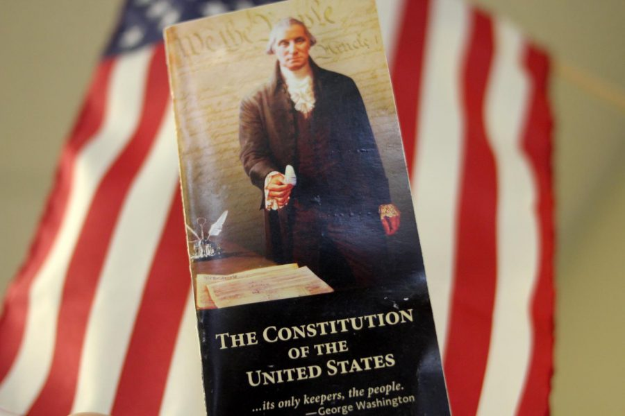With the American flag in the background, a pocket copy of the U.S. Constitution is held high. Constitution Day is Sept. 17, and marks the start of Freedom Week. During this week, students will engage with the Constitution through lessons and activities in their social studies courses.