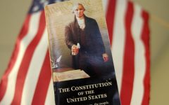 With the American flag in the background, a pocket copy of the U.S. Constitution is held high. Constitution Day is Sept. 17. Constitution day marks the start of Freedom Week.