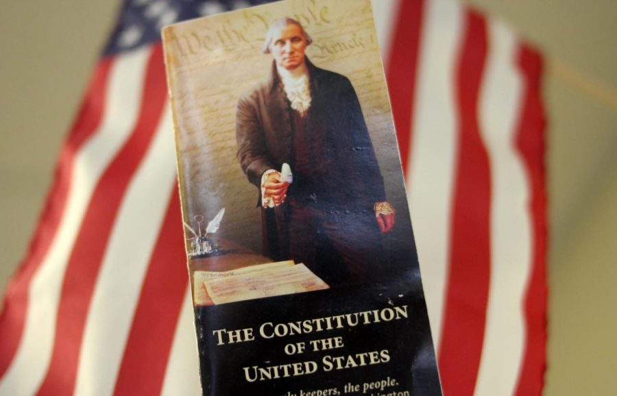 With+the+American+flag+in+the+background%2C+a+pocket+copy+of+the+U.S.+Constitution+is+held+high.+Constitution+Day+is+Sept.+17.+Constitution+day+marks+the+start+of+Freedom+Week.+