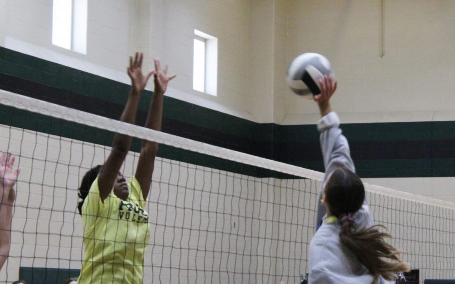 Bumping the ball over the net, the varsity volleyball girls practice. On Wednesdays, the volleyball teams wear yellow practice shirts. The volleyball girls will play their first district game Friday, Sept. 10, in the high school arena at 5:30 p.m. against Little Elm.