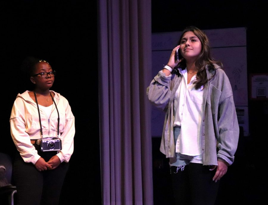 Phone in hand, Marjory, played by freshman Sophia Gomez, talks to her mom, as the Photographer, played by junior Seun Seriki, listens in. Gomez said she is most excited for the show days. It feels amazing to perform again and all the crew is amazing, Gomez said.