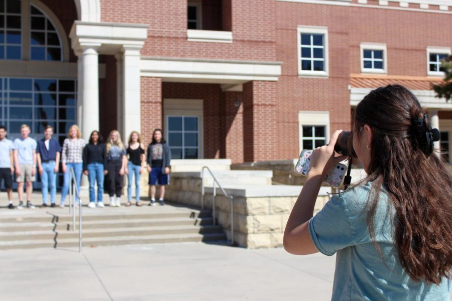 In front of the high school, sophomore Kaya Miller takes a photo of the National Merit Scholars. National Merit Scholars are seniors who scored above a certain number on the PSAT that they took in their junior year of high school. National Merit Semifinalists are Dennis Seibert and Reid Smith. Commended students include Sneha Algole, Makenna Brandvold, Casey Charleston, Tyler Cummings, Annmarie Graham, Alexander Kim, Charlie Koster, Meaghan McQueen, Elizabeth Myers, Erika Pedersen, Stephen Phillips, Kierstyn Schroeder, Jonathan Seo, Raquelle Smith, Hunter Springer and Drew Wessels.