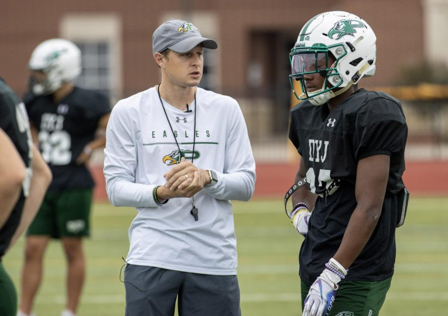 """After a drill, safeties coach Chase Petersen talks to junior safety Steven Richardson. Petersens eighth year coaching will be this year. """"Coach Petersen loves the kids he coaches, head coach Brandon Schmidt said. His goal is to see all of his players reach their full potential, and he will do whatever is necessary to help them."""""""