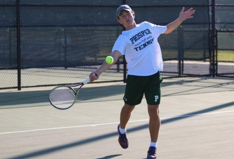 Swinging at the ball, junior Eli Steur prepares to hit the ball back over the net. He played doubles alongside junior Ridge Daniel. Steur played on varsity last year and is also in a cappella choir.