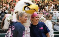 Talking to teachers Natalie Merrill and Jenny Mills, anatomy and physiology teacher Darilyn Krempin hugs Prestonwood Baptist Church member and teacher Holly Hollingsworth-Ervin. Mills, Krempin and Hollingsworth-Ervin are breast cancer survivors and were honored at the pep rally. It is important to honor Breast Cancer Awareness Month because it is time for us to not only advocate for the diagnosed women and men, but also to remember those who have previously lost their battle, senior Tiana Albino said. As we recognize this month, more and more people become educated when it comes to the signs and symptoms of breast cancer and ultimately save more lives we as promote awareness as a whole.